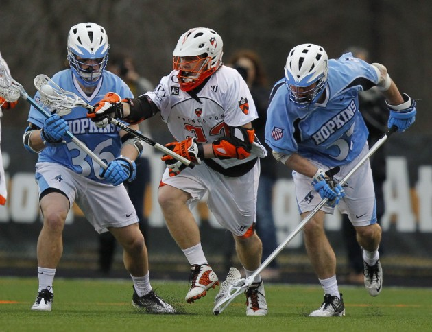 Mar 2, 2012; Princeton, NJ, USA; Princeton Tigers midfielder Tom Schreiber (center) brings the ball up field against John Hopkins Blue Jays defenders Nikhon Schuler (36) and Tucker Durkin (51) at Princeton. Mandatory Credit: Jim O'Connor-USA TODAY Sports